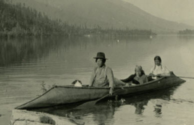 A young family in a sturgeon-nosed canoe on Kootenay Lake.